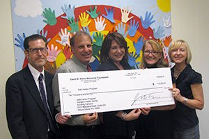 David B. Weiss Foundation team presents check to AMH Safe Harbor team
